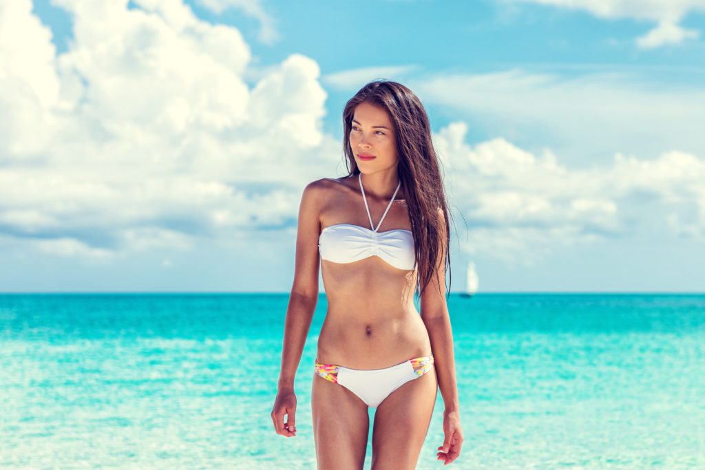 Woman in a bikini standing in front of the ocean