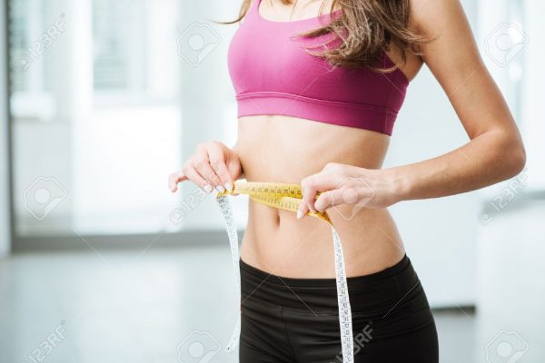 43397067-slim-young-woman-measuring-her-thin-waist-with-a-tape-measure-close-up